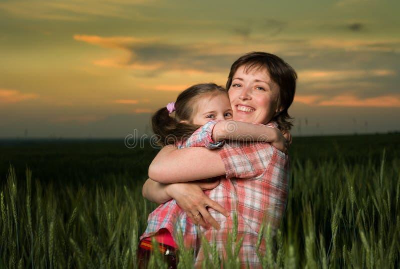 Семья мамы и дочери на заходе солнца стоковые изображения