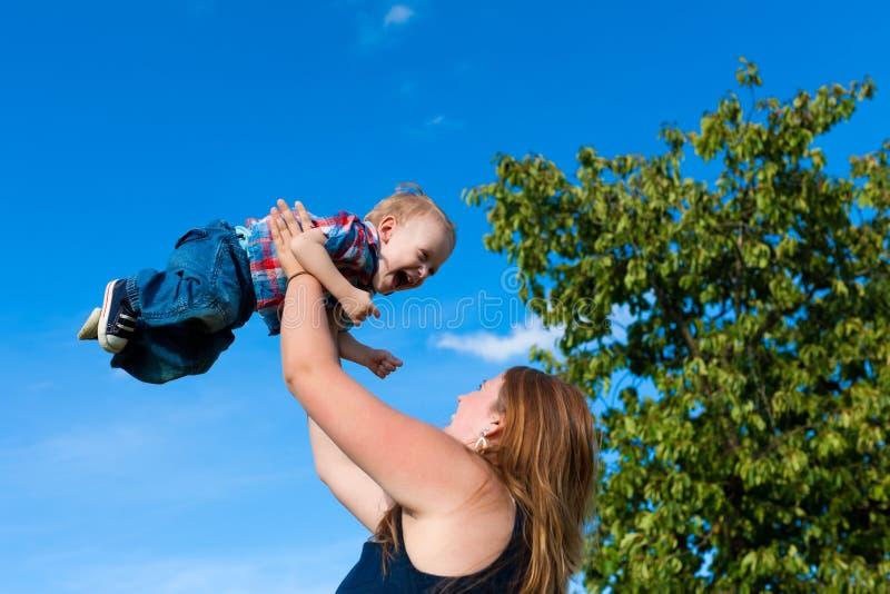 Семья - мать и ребенок играя в саде стоковая фотография rf