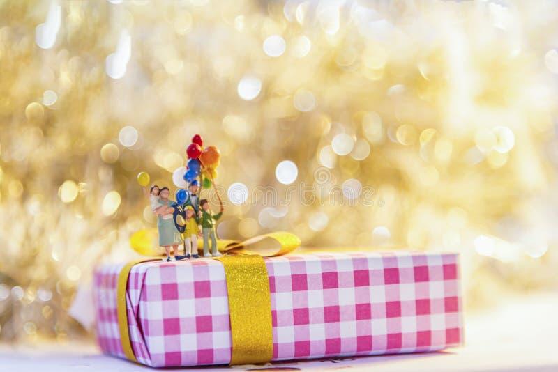 Семья миниатюрной группы счастливая держа воздушные шары стоя на wi коробки стоковая фотография