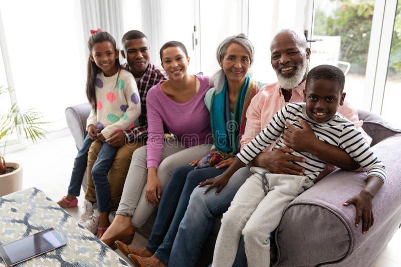 семья Мульти-поколения ослабляя совместно на софе в живя комнате дома стоковые фото