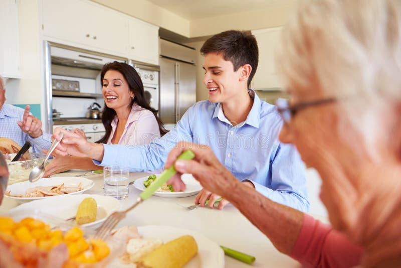 Семья Мульти-поколения сидя вокруг таблицы есть еду стоковые изображения rf
