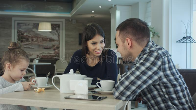 Семья наслаждаясь чаем в кафе совместно Отец и мать говоря смотрящ их дочь стоковые изображения rf