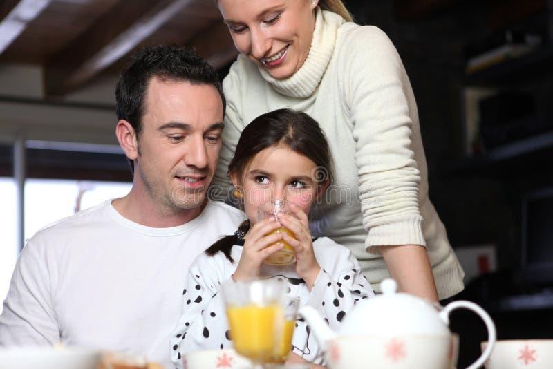 Семья наслаждаясь завтраком стоковое фото