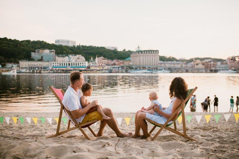 Семья на взморье в выравнивать под открытым небом кафе Мать и отец и 2 сынов сидят на шезлонгах, смотря заход солнца на песчаном  стоковое изображение rf