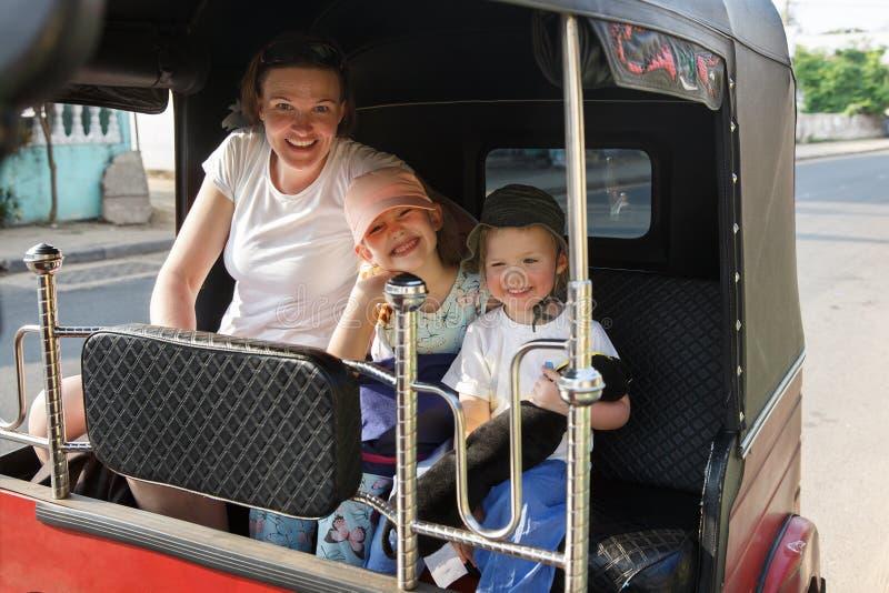 Семья на каникулах, мать и дети сидя в мото-такси, имеющ потеху стоковые фотографии rf