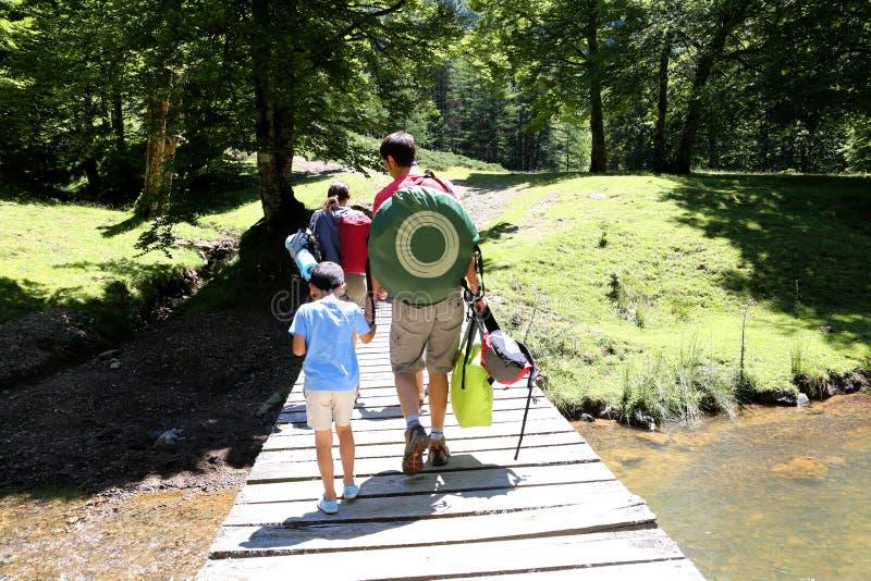 Семья на пешем реке скрещивания отключения на мосте стоковые фотографии rf
