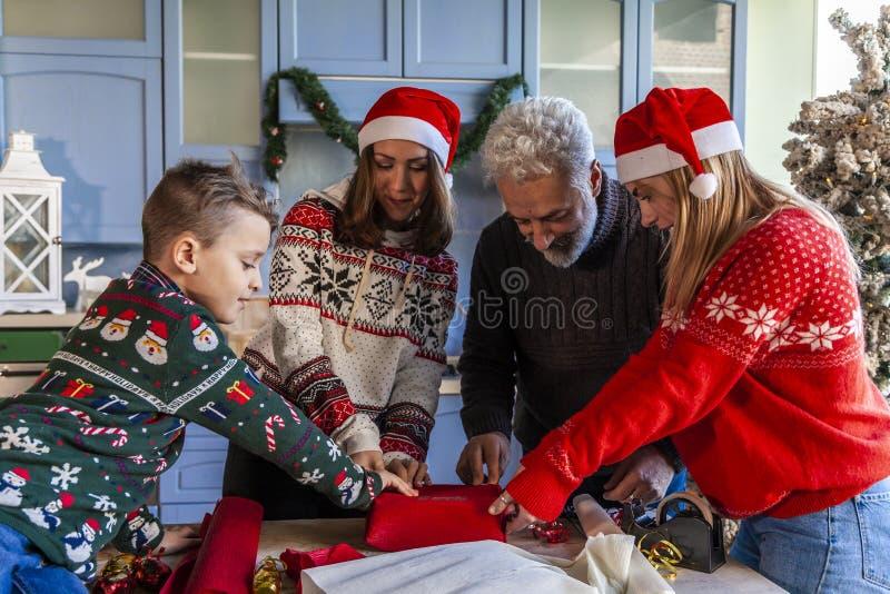 Семья на Рождество пока подготавливающ подарок стоковые фотографии rf