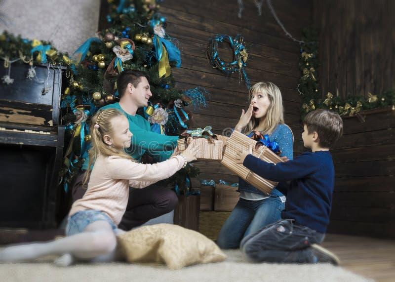 Семья обменивая подарки перед елью рождества стоковые фото