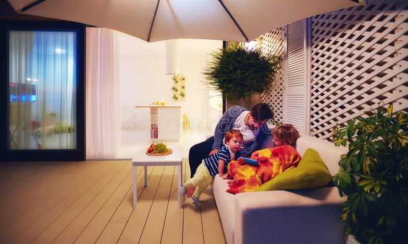 Семья ослабляя на зоне патио с кухней и раздвижными дверями открытого пространства на предпосылке стоковые фотографии rf
