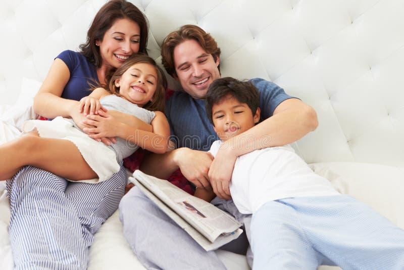 Семья ослабляя в кровати с кофе и газетой стоковое фото