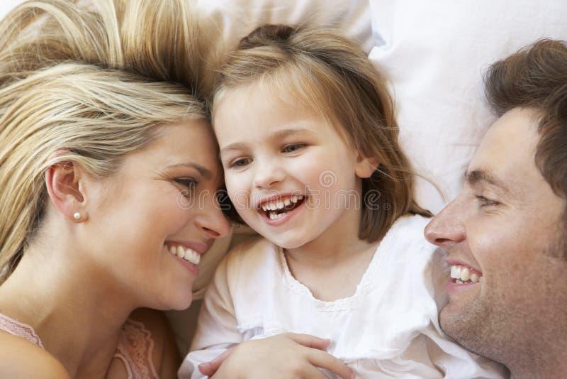 Семья ослабляя в кровати стоковые фотографии rf