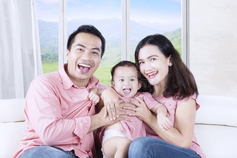 Семья ослабляя на софе и смеясь над совместно стоковые фото