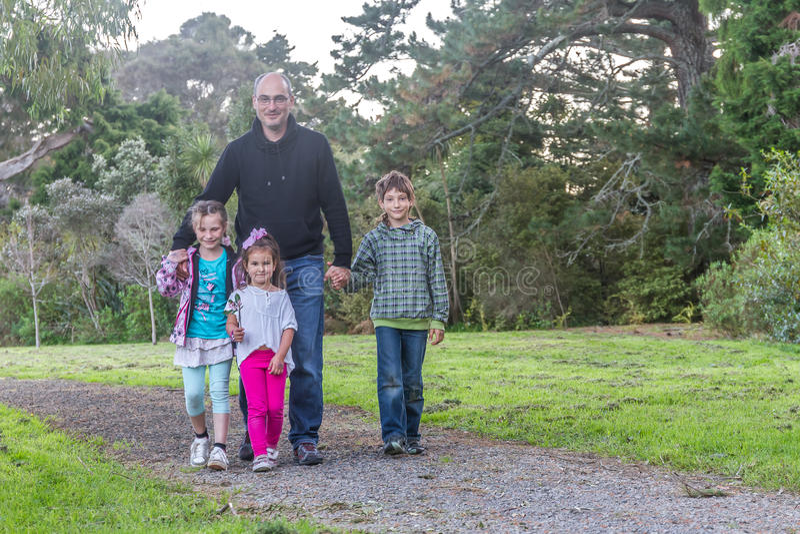 Семья - отец и дети - в парке стоковое изображение rf