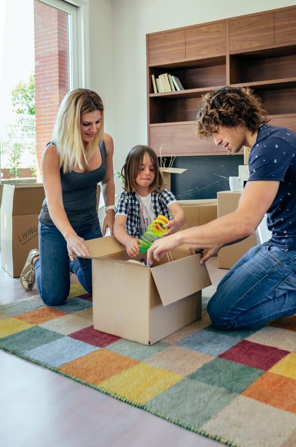 Семья подготавливая moving коробку для игрушек стоковые изображения rf
