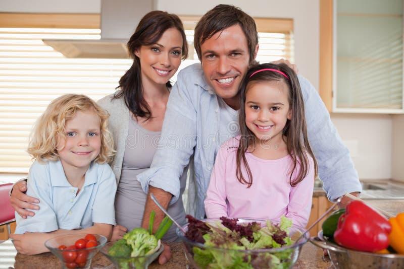 Семья подготовляя салат стоковое фото