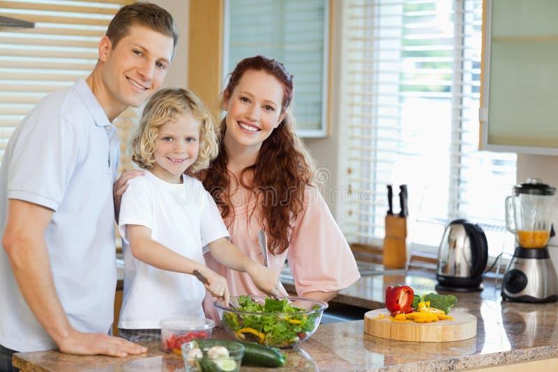Семья подготовляя салат стоковая фотография