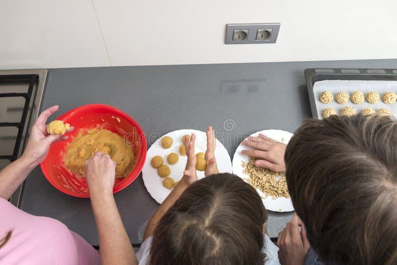 Семья подготавливая помадки в кухне стоковое фото rf