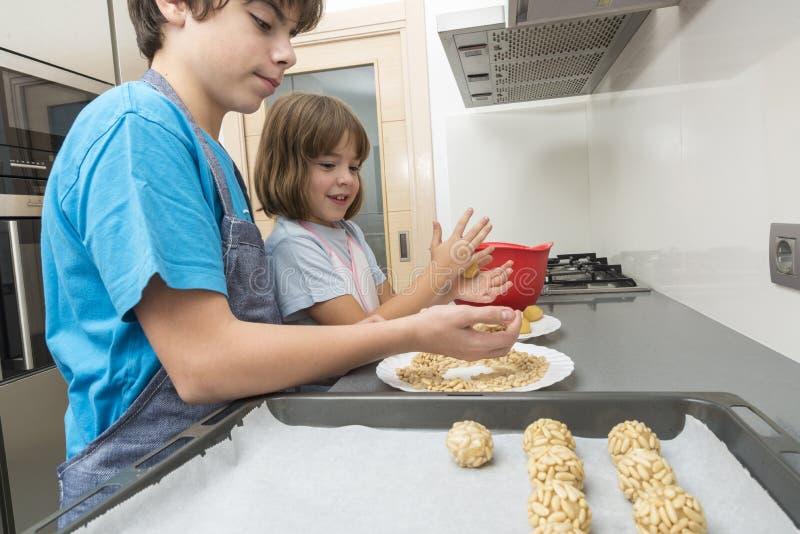 Семья подготавливая помадки в кухне стоковые фотографии rf