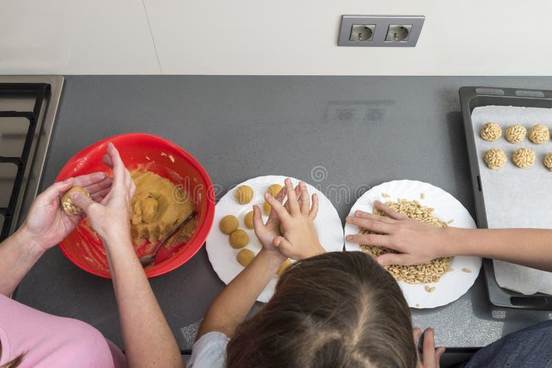 Семья подготавливая помадки в кухне стоковое фото