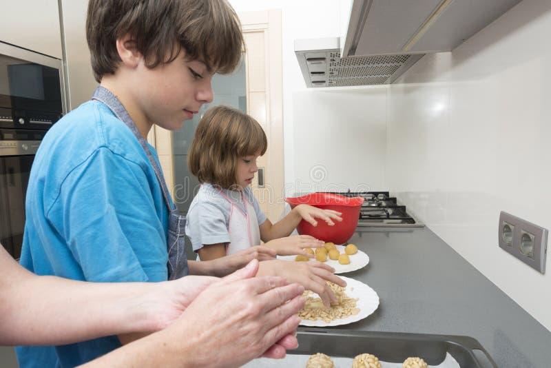 Семья подготавливая помадки в кухне стоковое изображение