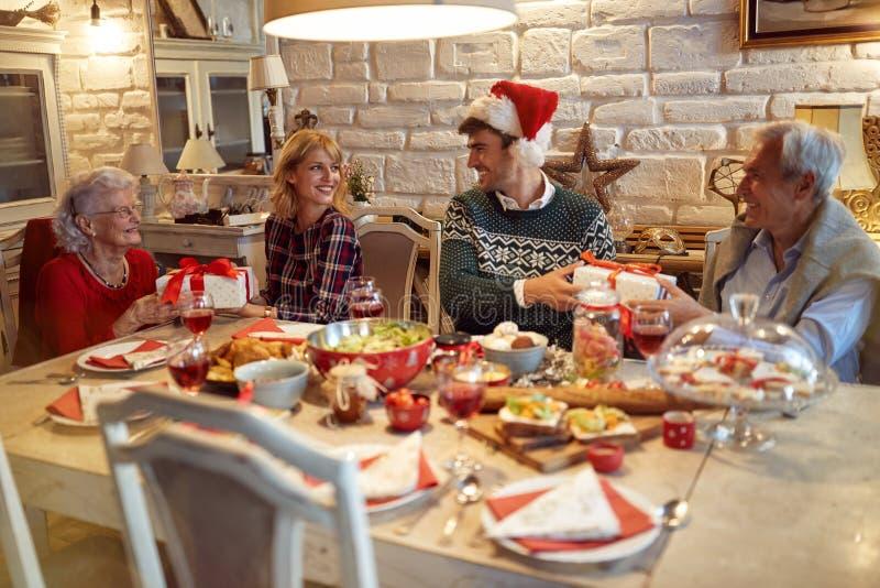 Семья празднует рождество дома и дающ подарок на рождество стоковые фото