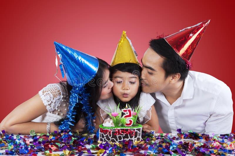 Семья празднует день рождения с красной предпосылкой стоковое изображение rf