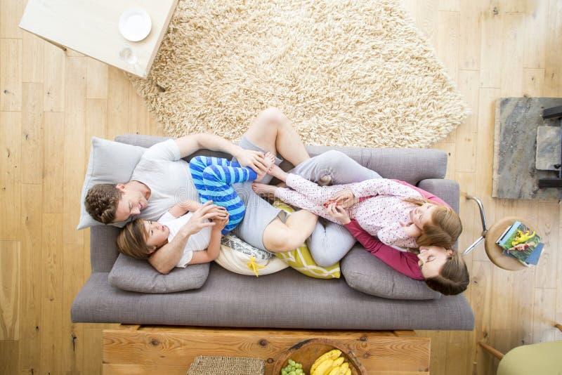 Семья прижимается на софе стоковые изображения rf