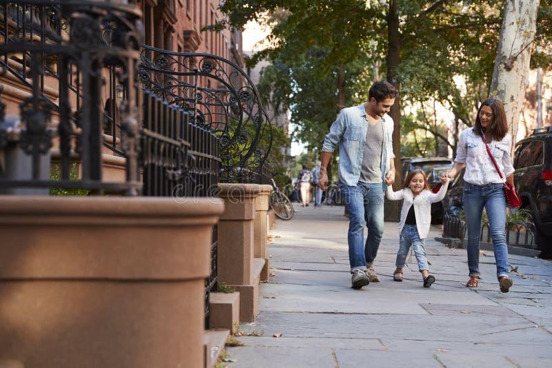 Семья принимая прогулку вниз с улицы стоковая фотография rf