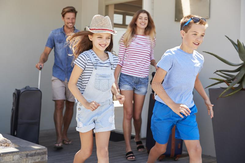 Семья при багаж покидая дом на каникулы стоковые фото