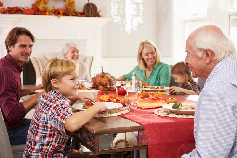 Семья при деды наслаждаясь едой благодарения на таблице стоковые фотографии rf