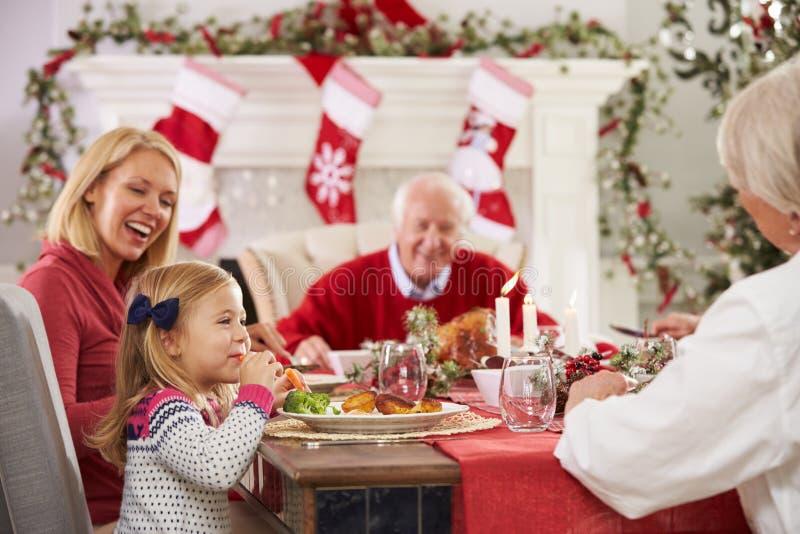 Семья при деды наслаждаясь едой рождества на таблице стоковые фотографии rf