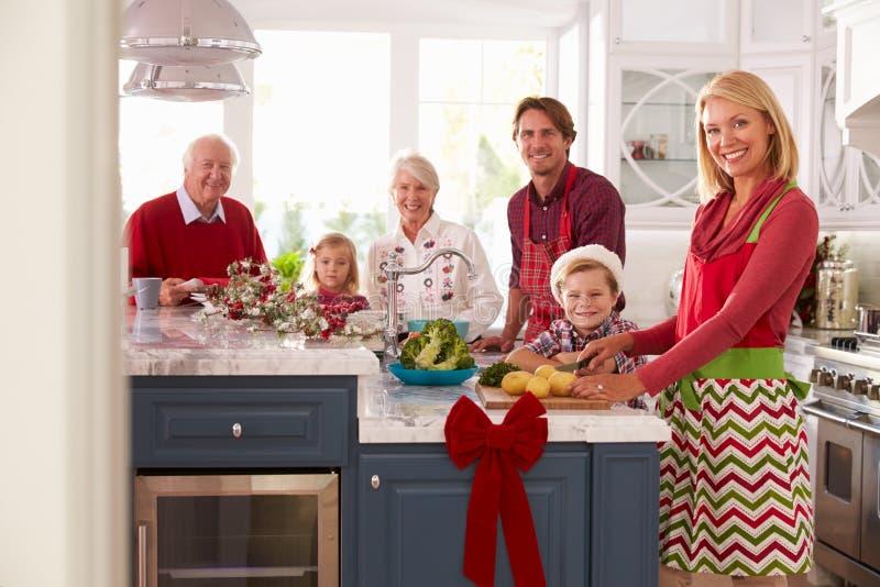 Семья при деды подготавливая еду рождества в кухне стоковые изображения