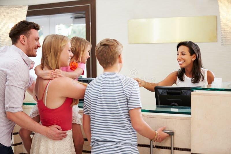 Семья проверяя внутри на приеме гостиницы стоковое фото