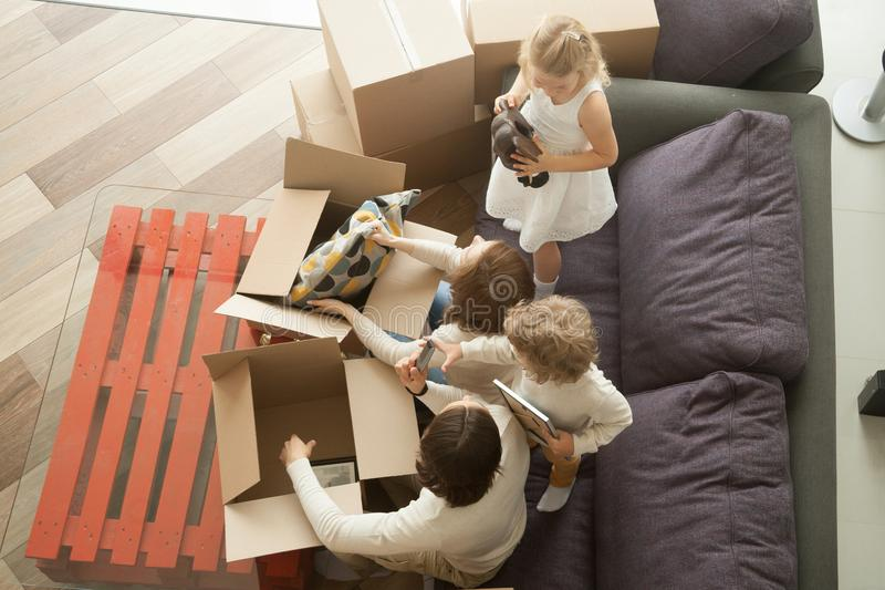 Семья распаковывая коробки совместно двигая в новый дом, взгляд сверху стоковое изображение rf
