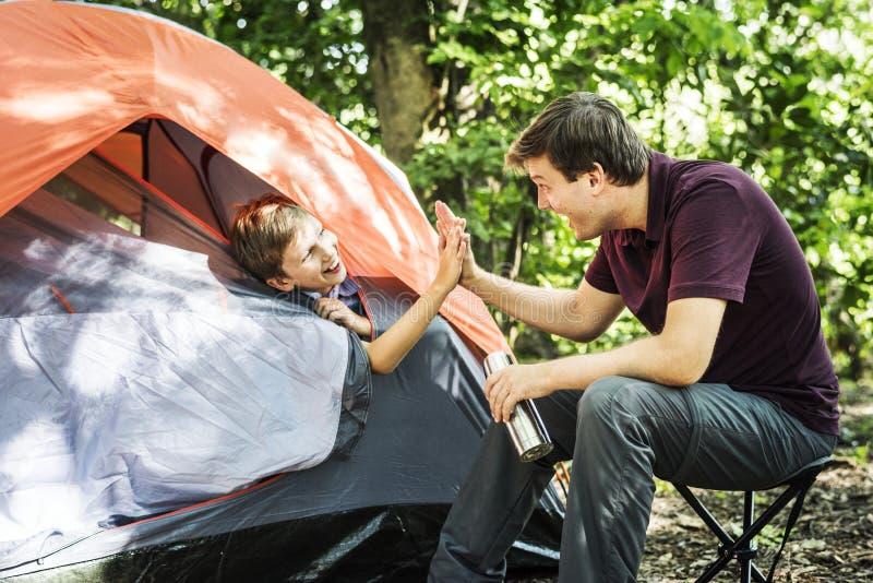 Семья располагаясь лагерем в лесе стоковое изображение