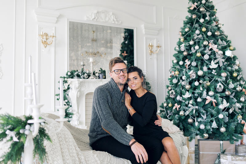 Семья, рождество, праздники, влюбленность и концепция людей - счастливая пара сидя на софе дома стоковое изображение rf
