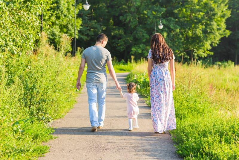Семья, родительство и концепция людей - счастливые мать, отец и маленькая девочка идя в лето паркуют стоковое изображение rf