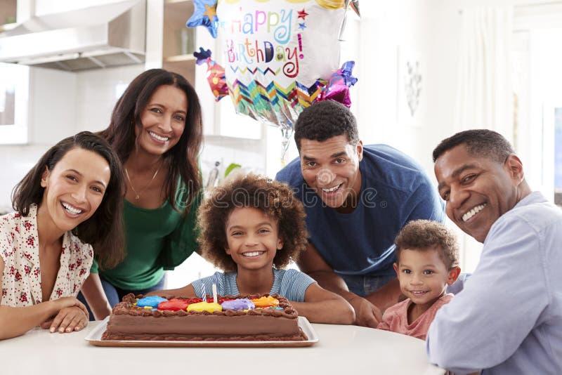 Семья семьи 3 поколений Афро-американская собранная в кухне празднуя день рождения совместно, смотрящ к smilin камеры стоковая фотография