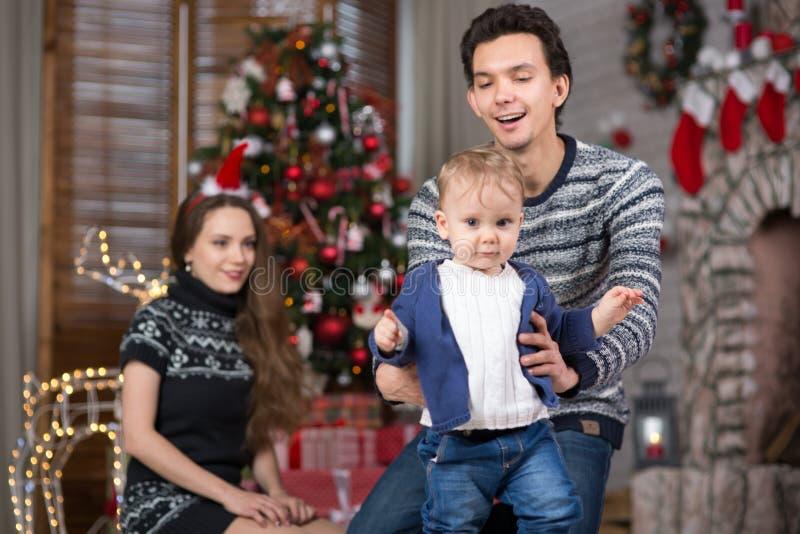 Семья сидит с младенцем сидя около рождественской елки стоковая фотография