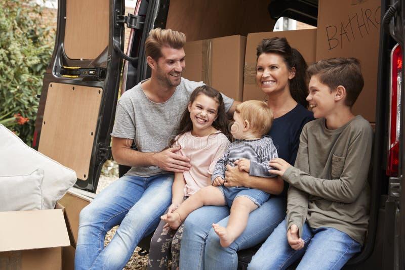Семья сидя внутри подпирает тележки удаления на Moving день стоковые фото