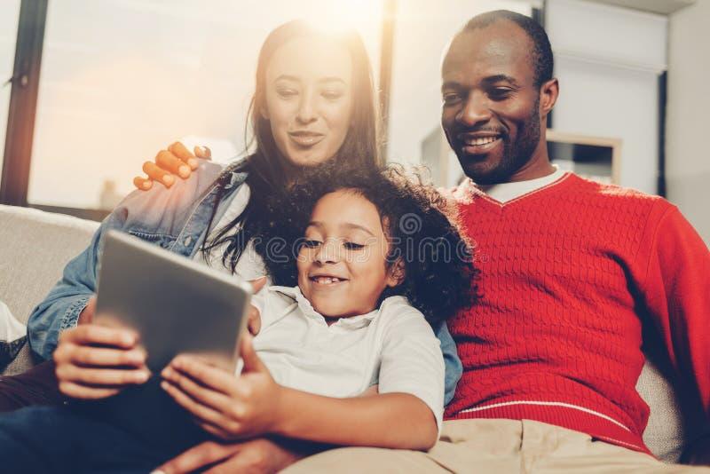 Семья сидя внутри помещения и наслаждаясь современной технологией стоковое изображение rf