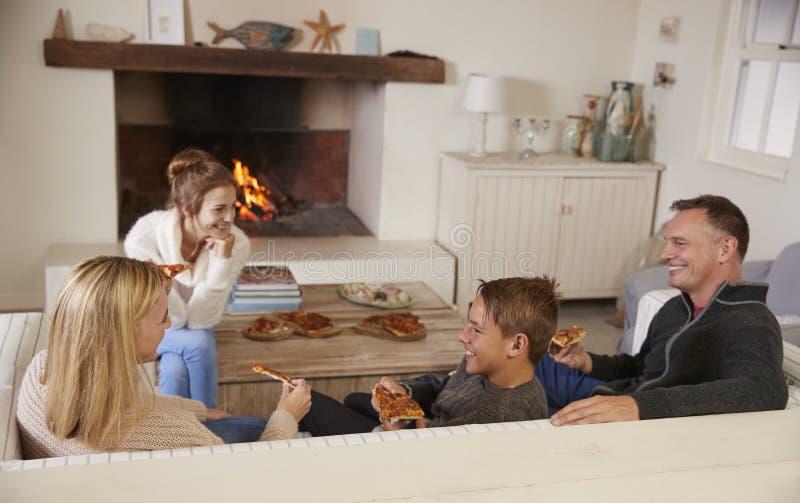 Семья сидя на софе в салоне рядом с открытым огнем есть пиццу стоковые фото
