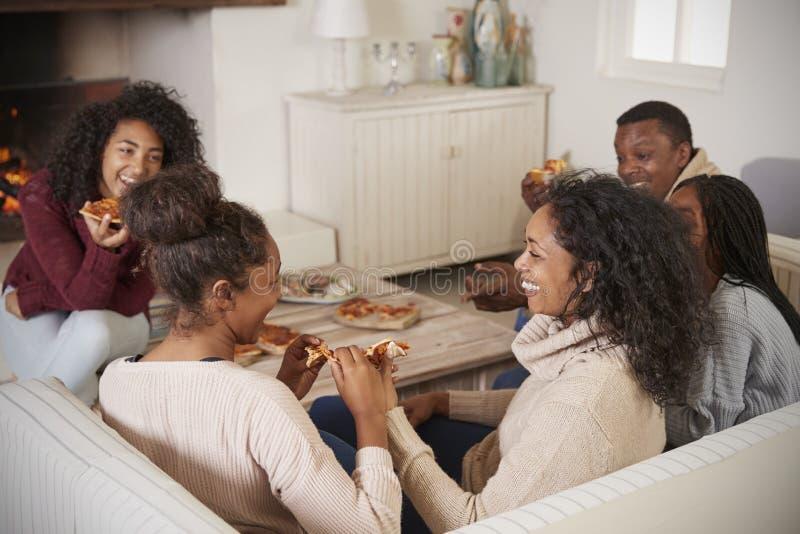 Семья сидя на софе в салоне рядом с открытым огнем есть пиццу стоковое изображение