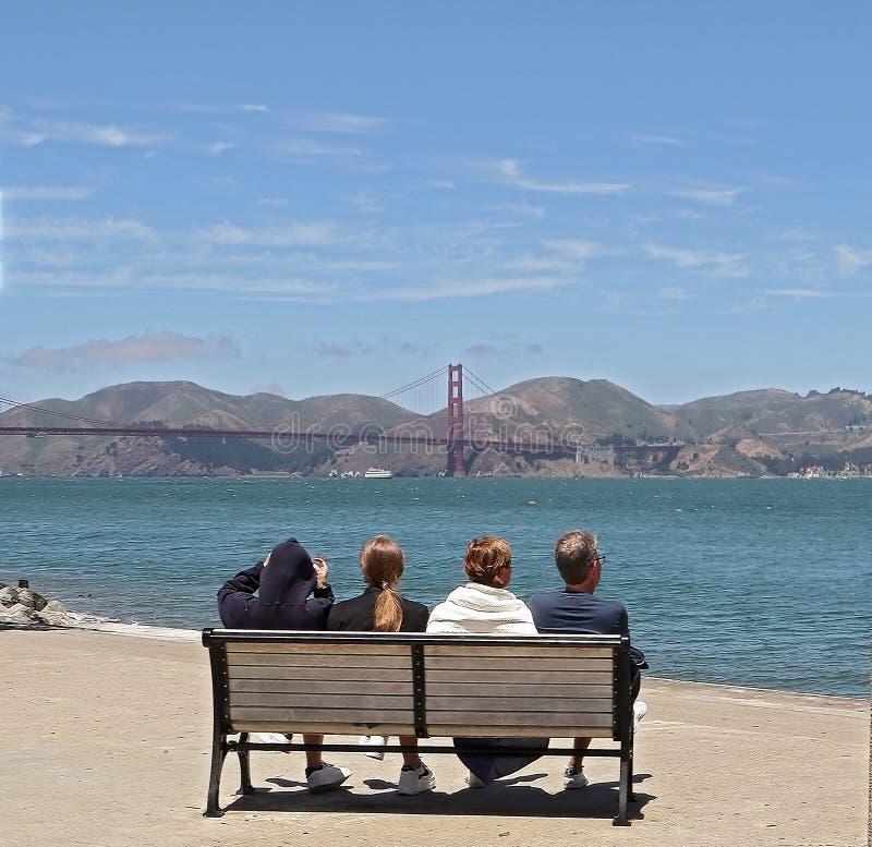 Семья сидя на стенде и наслаждаясь взглядом моста золотых ворот в Сан-Франциско, Калифорния стоковое фото rf