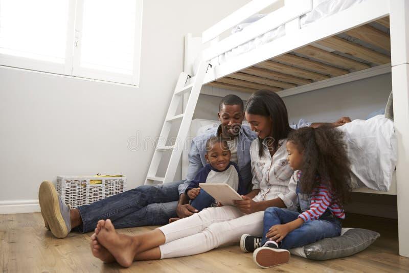Семья сидя в спальне используя таблетку цифров совместно стоковая фотография