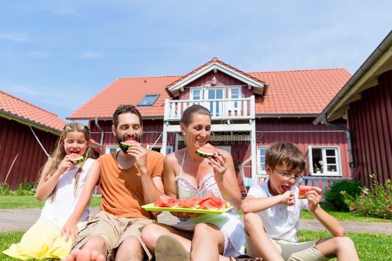 Семья сидя в фронте травы домашнего арбуза еды стоковая фотография rf