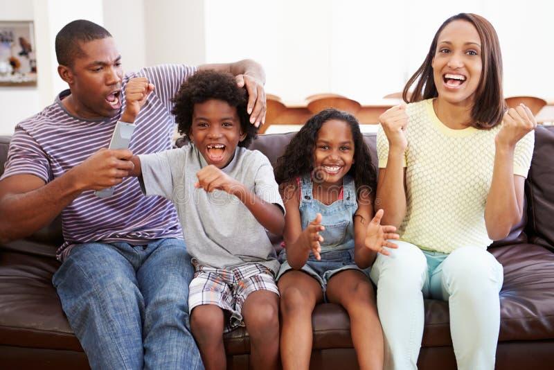 Семья сидя на софе смотря ТВ совместно стоковые фотографии rf