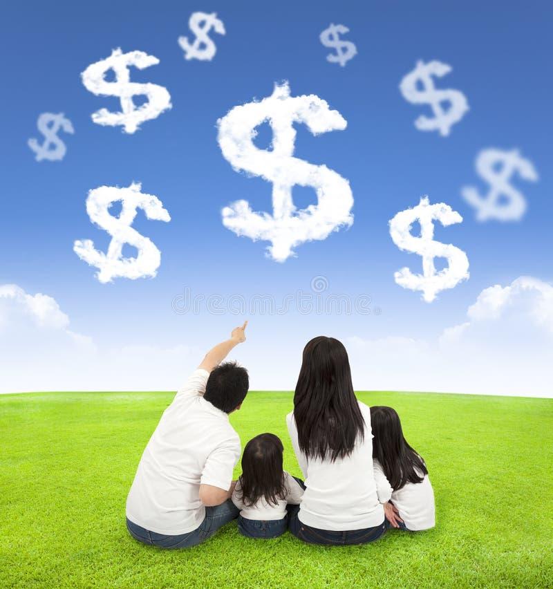 Семья сидя на луге с деньгами облаков стоковые фото