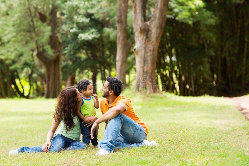 Семья сидя outdoors стоковое изображение rf