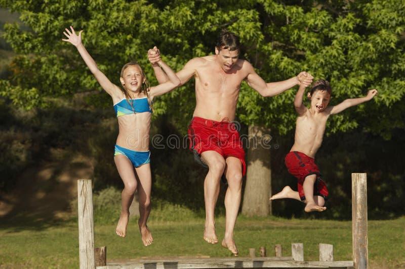 Семья скача в озеро стоковые изображения rf